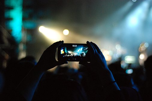music festival taking video on phone of artist